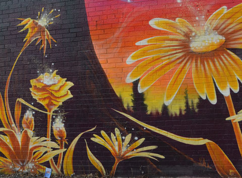 part of a larger mural, yellow daisy like flowers growing on a black background with a large yellow, orange and red circle in the background.