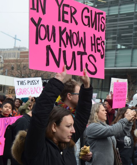 Womens March, toronto - a woman holds a large pink sign up over her head that reads In yer guts you know he's nuts. She's walking with many other people