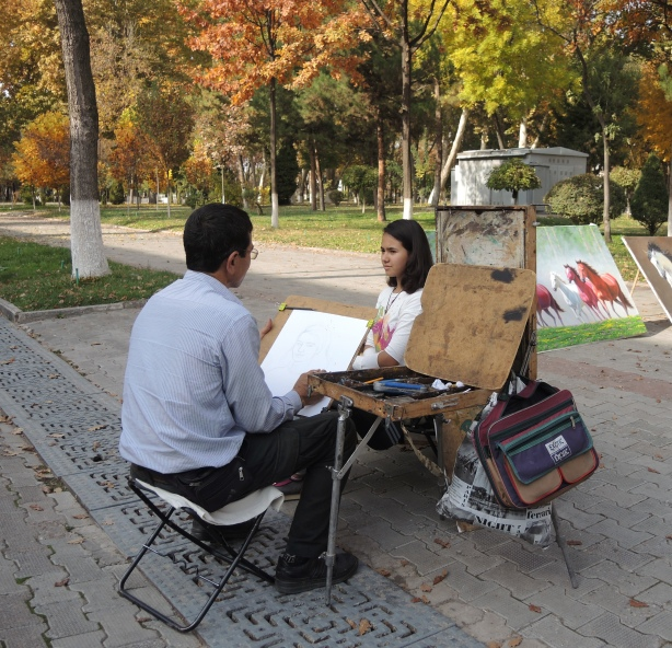 a man is drawing a portrait of a young woman, outdoors