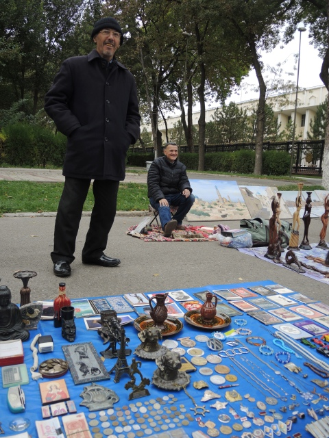 two men are selling items on the sidewalk. They have the things laid out on a blue piece of fabric