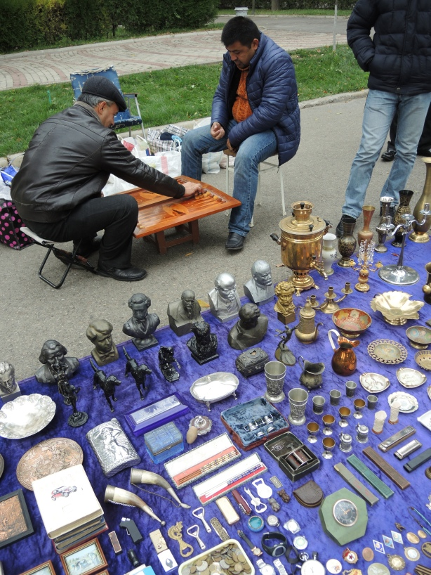 two men play backgammon at a low table while they wait for people to buy things they are selling outdoors.