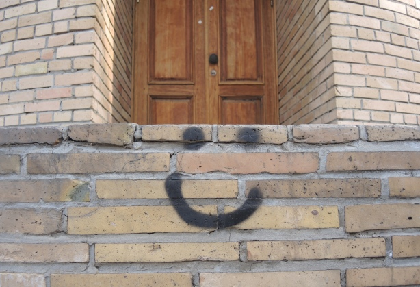 a happy face in black spray paint on the bricks at the base of a minaret, a small piece of graffiti