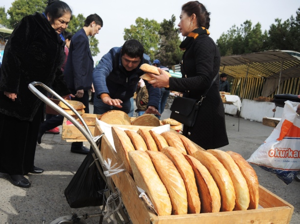 selling round loaves of bread from a cart at the outdoor market in Tashkent