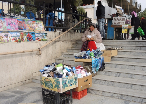 sitting on the steps outside the covered market, a woman sits with boxes of goods to sell