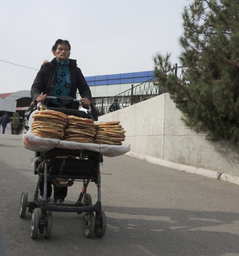 a man pushes a small cart on which there are flat circular loaves of bread to sell