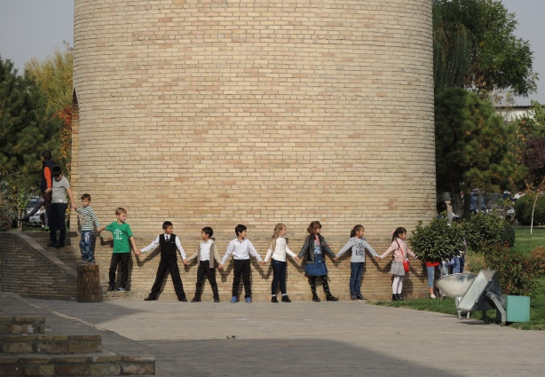 school children link hands to form a cirlce around the base of a minaret
