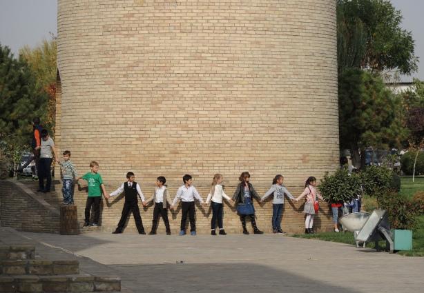 school children link hands to form a cirlce around the base of a minaret