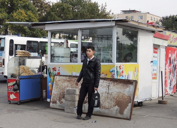 a boy waits for a bus at a bus stop