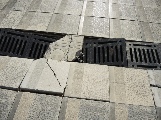 broken tiles on the sidewalk and broken metal drain covers as well