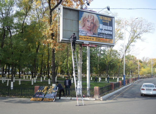 two men are changing a billboard by hand. Each strip of the picture has to be changed