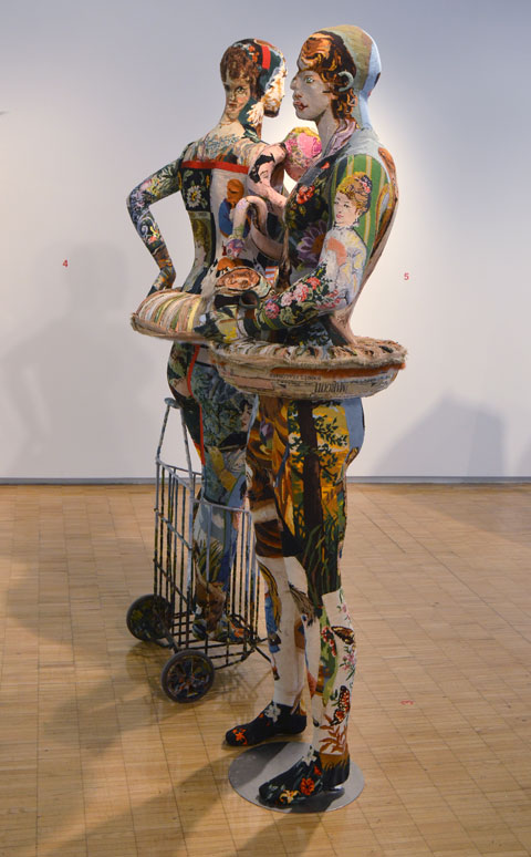 two mannequins covered in patchwork of tapestry needlepoint with pictures that sort of match the anatomy of the mannequin.   The faces dont quite line up,   a man and a woman.  the woman is standing in a shopping cart