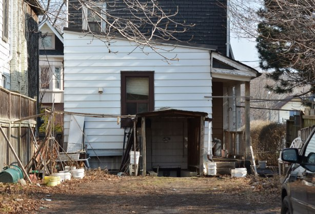 side yard and side entrance to a wood clapboard house with one window on the side at ground level.