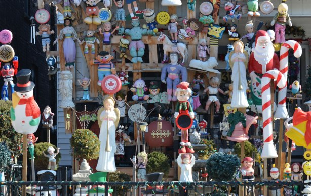 a massive collection of dolls, toys, stuffed animals and decorations fill a front yard of a house