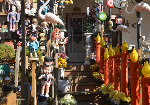 frontyard of a house is full of toys and decorations, the front walk is lined by large plastic red candles, the front door is in shadows.