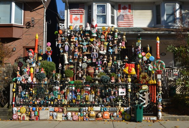 the front yard of a semi detached house is full of toys and stuffed animals, signs and flags, and Christmas decorations,