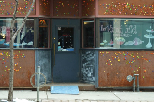 store front, front of Bettys bar and restaurant, with grey door. Walls are magnetic and they are covered with kid's letters of the alphabet magnets.