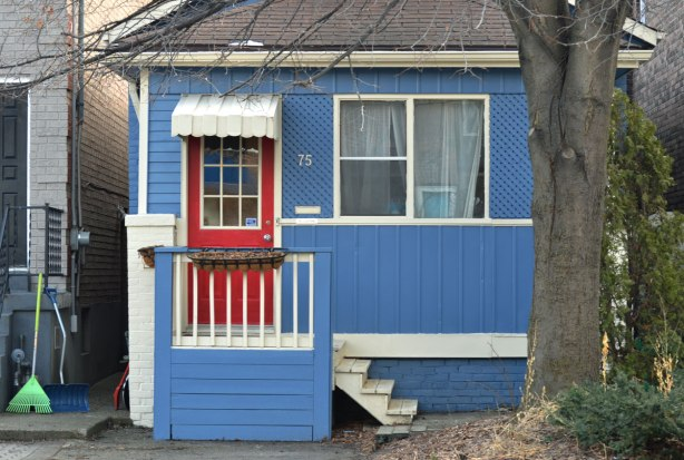 a small house painted blue with white trim, a bright red door.