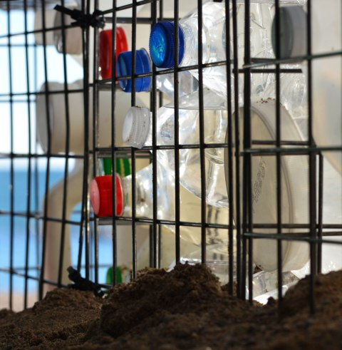 empty plastic bottles in a wire cage sits on the sand of the beach