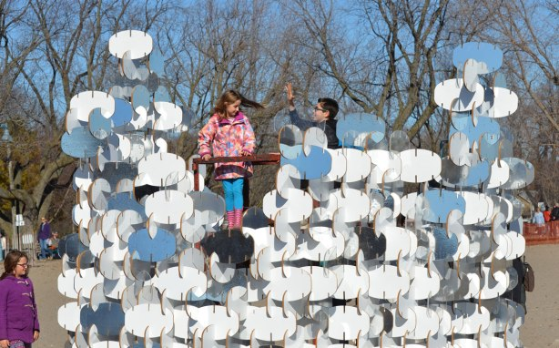 kids climb up the center of an art installation called buoy buoy buoy, standing on the lifeguard station platform that is the middle of the artwork. Made of wooden oval shapes that are notched together.