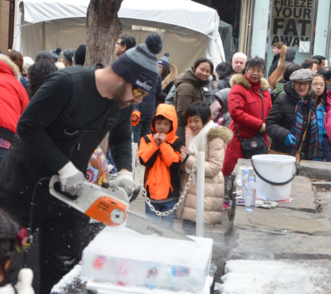 a man is using a chainsaw to cut a chunk of ice into smaller cubes. Small toys have been frozen into the ice. Other people are watching, especially two kids.