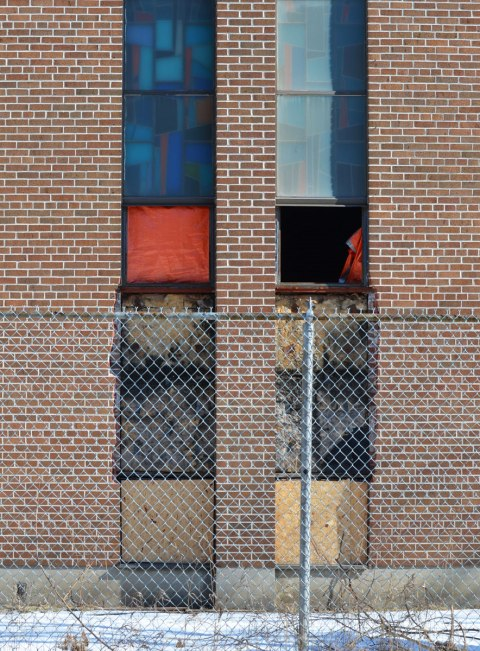 vertical windows on a birck church, behind a chain link fence. Two of the windows have panes missing and are covered with orange cloth