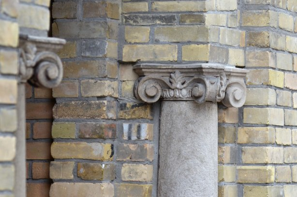 a small column with an ionic like capital, embedded in a brick wall. The column looks to be supporting an arch over the doorway