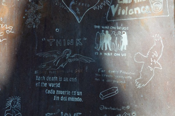 part of a metal memorial for people who died of drugs and AIDS, Counter fit (a harm reduction organization). people have scratched words and drawings into the metal, a dove, a heart, words like The war on drugs is a war on us