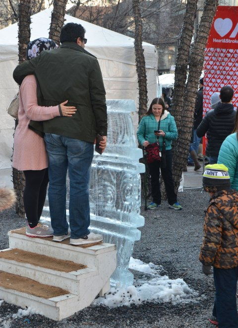 a coouple stand on a set of stairs behind an ice sculpture to have their picture taken.