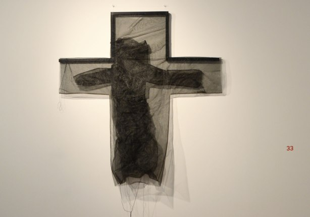 black netting in the shape of a cross on a wall. within the cross is more black light weight fabric in the shape of a person whose arms in the horizontal parts of the cross.