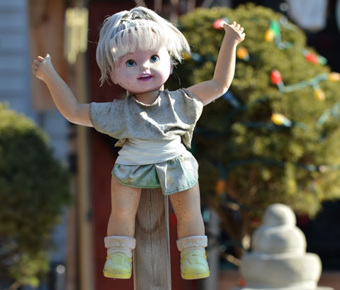 a small smiling doll with her arms up is attached to a wooden stake in the front yard of a house