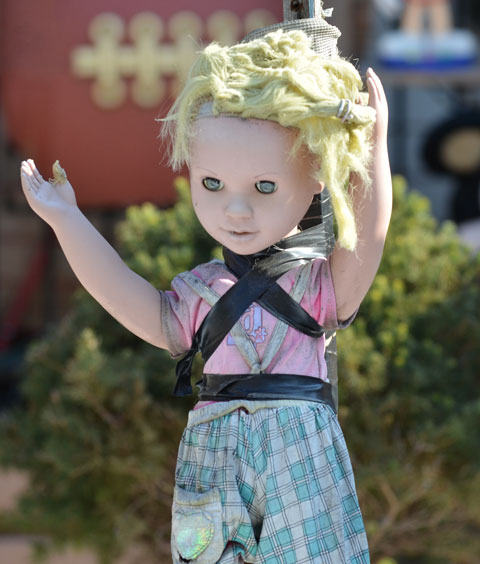 a faded blond doll with blank eyes looks down, she is attached to a wooden stake with black electrical tape