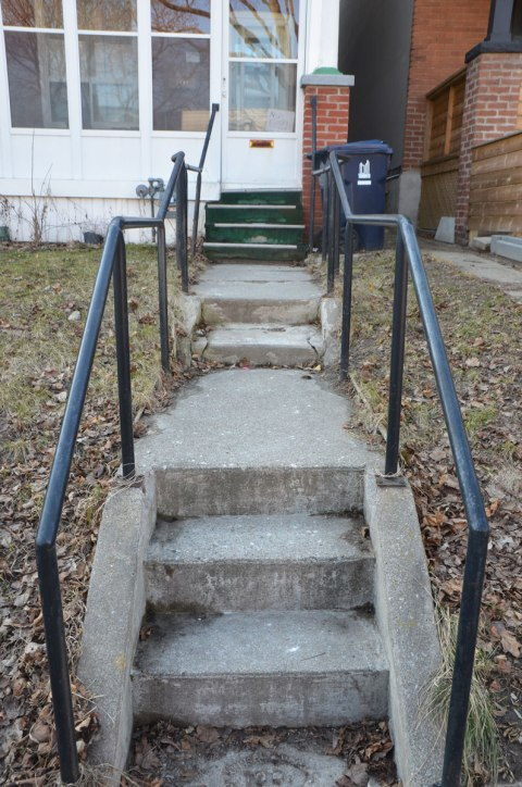 crooked concrete steps and metal railing lead to a front door.