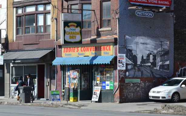 looking diagonally across the steet to Eddie's convenience store with it's old Canada Dry ad sign hanging over the doorway and the black and white mural taken from a view of Queen St. East long ago.