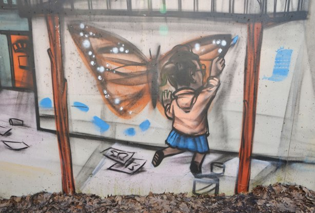 mural by elicser in the tunnel that is a railway underpass - a girl is painting a large picture of a monarch butterfly on a wall