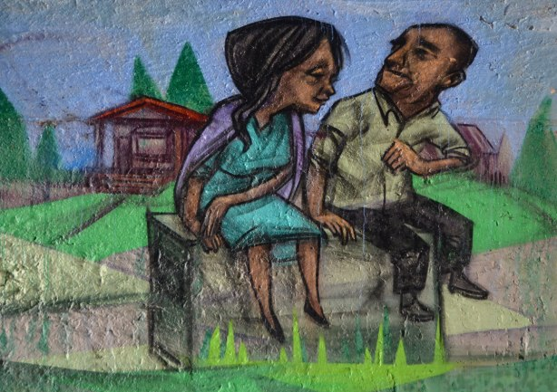mural by elicser in the tunnel that is a railway underpass - a couple sits on a bench, a cabin is behind them