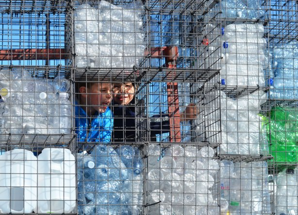 two boys peer out from behind a wall of wire cages filled with empty plastic bottles. One of the cages is empty as looks like a window