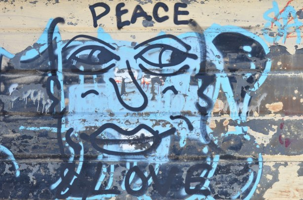 painting on a garage door, black line drawing of a face on blue with peace written above and love written below the face