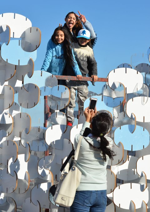 three kids stand on top of a lifeguard station that is enclosed by an art installation that is construction of many oval shapes joined together. Some are white, some are clear and some are reflective. A mother is taking a picture of the kids.