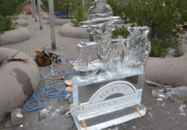 an ice sculpture of a mountie and a beaver has just been finished. The tools used by the artist are lying around on the ground below the sculpture.