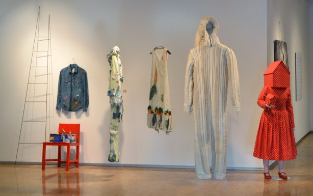 a row of designer clothes as part of an art gallery ehbiti, a paint splotched covered blue long sleeved shirt, a red mid-calf length red dress with white polka dots with little red school house shaped head on the mannequin, and and holding a small red schoolhouse in her hand, a sleeveless dress with carrots in many pockets