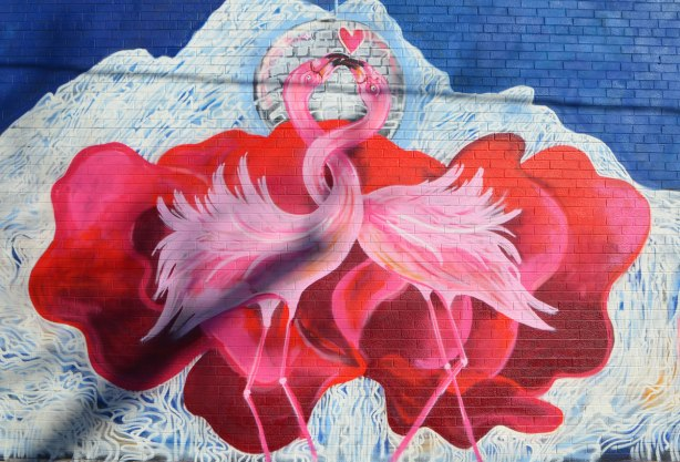 part of a largeer mural of two pink flamingoes with the necks intertwined and their beaks together in a kiss, red petals behind them.
