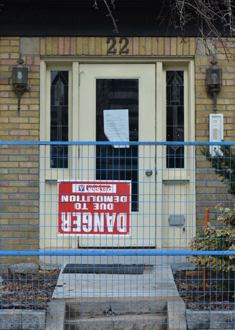 the front door of a small apartment complex that is about to be demolished. There is a blue metal fence in front of it with a danger due to demolition sign on it. The sign is upside down.