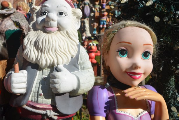 a white plastic gnome and a Disney princess are among a large collection of toys in a front yard