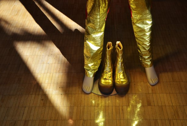 a mannequin in shiny gold pants stands with its feet apart, in between its feet are a pair of shiny gold boots