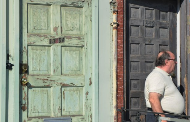 two doors, one faded green and one greyish black . a man with a rather large stomach is standing in front of the latter.