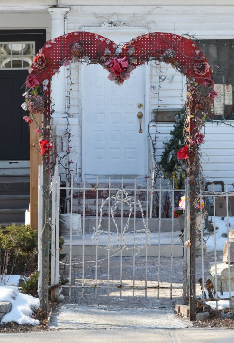 a small archway over a gate at the entrance to a front yard, the arch is the shape of a heart and it has been decorated with flowers.