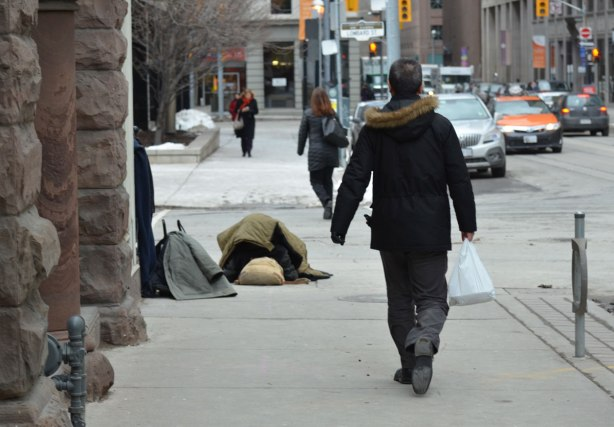 people walk by on the sidewalk as a homeless man sleeps under blankets on the corner.