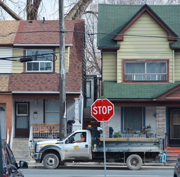 looking down a street to an T-intersection. Two houses across the intersection with a large truck parked in front of them. A man is sitting in the truck and looking at the camera