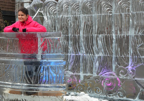 a girl in a bright pink jacket stands behind a podium built of ice and in front of a wall made of ice. Both have curvy lines and swirls carved into them.
