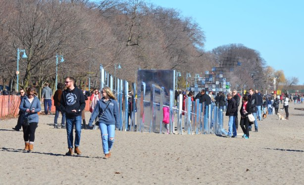 lots of people walking past and looking at two art installations on the beach as part of Winter Stations event